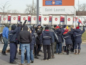 Striking Canada Post workers walk the picket line in front of the Saint-Laurent sorting facility in Montreal on Thursday, Nov. 15, 2018.