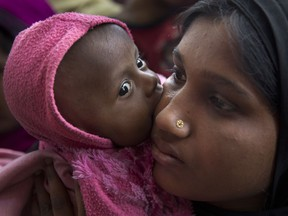 A newly arrived Rohingya refugee child licks the cheek of her mother Azida Khatoon, 20, as they wait in a food distribution line in the Kutupalong refugee camp near Cox's Bazar, Bangladesh on Jan. 27, 2018. The stripping and denial of citizenship has encouraged discrimination, persecution and violence against stateless people. For example, the genocide of Rohingya was precipitated by their being denied citizenship in Myanmar, a country they called home for generations.