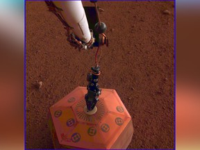 This photo provided by NASA Jet Propulsion Laboratory, shows the new Mars lander placing a quake monitor on the planet's dusty red surface.