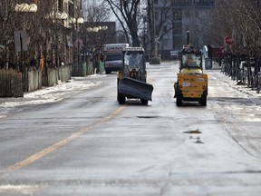 Snow removal crews speak for a moment while heading to refill with abrasives along Atwater St. in Montreal, Jan. 1, 2019.