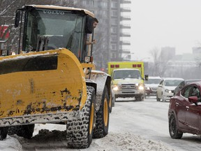 A snow-removal worker moves his vehicle onto the sidewalk and gestures to motorists to make way for an ambulance on Cote-des-Neiges Rd. on Wednesday January 23, 2019.