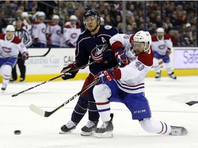 Canadiens' Michael Chaput, right, shoots the puck against Columbus Blue Jackets' Cam Atkinson in Columbus, Ohio, on Friday, Jan. 18, 2019.