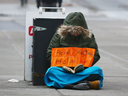 A homeless person panhandles in downtown Calgary.