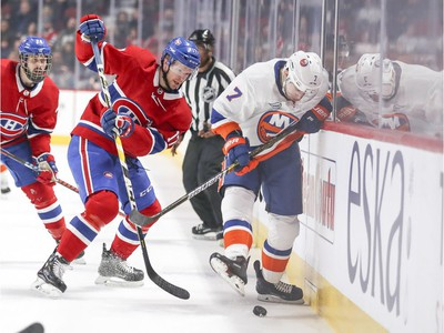 Montreal Canadiens' Philip Danault, left, and Brett Kulak watch as New York Islanders' Jordan Eberle kicks the puck away from the side boards during first period of National Hockey League game in Montreal Thursday March 21, 2019.
