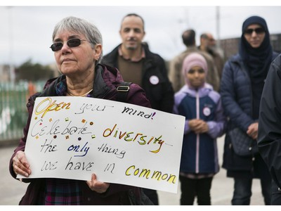 A woman holds a sign as she and others  listen to speakers at a Rally For Religious Freedom and against the CAQ government's Bill 21 in Côte-St-Luc on Sunday, April 14, 2019.