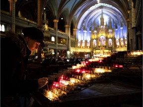 A woman lights a candle at Notre-Dame Basilica in Montreal, on Tuesday, April 16, 2019.