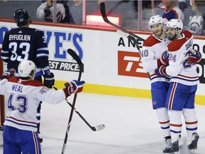 Montreal Canadiens' Jordan Weal (43), Joel Armia (40) and Phillip Danault (24) celebrate Armia's goal on the Winnipeg Jets during first period action in Winnipeg on March 28, 2019.