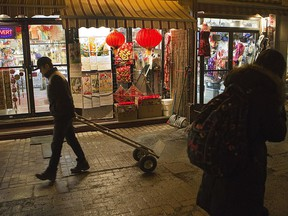 """People walk along de la Gauchetière St.: """"Chinatown is still a home for many elderly residents, and a critical meeting place for newcomers and long-time community members of Chinese and Asian descent,"""" Sarah M. Mah writes."""