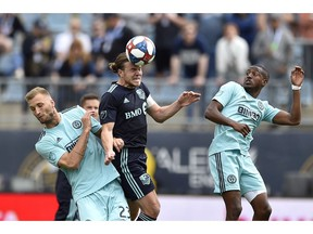 Montreal Impact's Samuel Piette, centre, heads the ball past the defence of Philadelphia Union's Kacper Przybylko, left, and Fafa Picault during the second half of MLS match on April 20, 2019, in Chester, Pa.