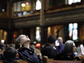 A woman cries as the organs begin to play at Notre Dame Basilica April 16, 2019.