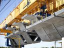 One of two custom built cranes lifts prefabricated concrete sections in to place for the REM rail line.