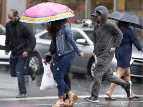 People huddle under umbrellas or run to cross the street during a downpour in Montreal June 25, 2019.