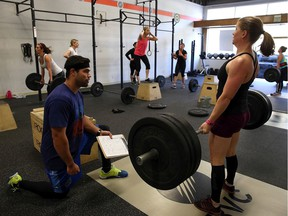 CrossFit coach Kory Cook (L) watches Erin Lindheim (R) do a deadlift during a CrossFit workout at Ross Valley CrossFit on March 14, 2014 in San Anselmo, California. CrossFit, a high intensity workout regimen that is a constantly varied mix of aerobic exercise, gymnastics and Olympic weight lifting, is one of the fastest growing fitness programs in the world.