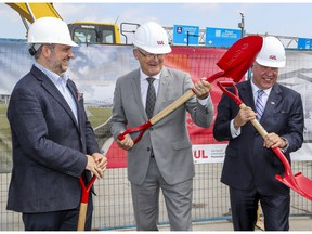 Federal Transport Minister Marc Garneau is seen standing between Montreal executive committee chairperson Benoît Dorais, left, and Philippe Rainville, president and director-general of ADM Aéroports de Montreal,  at ground-breaking ceremony for construction of the REM station at Trudeau airport in Dorval on July 19, 2019.