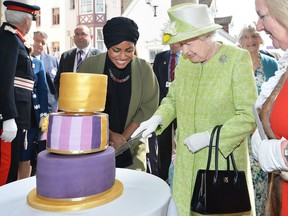 Queen Elizabeth II receives a birthday cake from Nadiya Hussain, winner of the Great British Bake Off, during her 90th Birthday Walkabout on April 21, 2016 in Windsor, England.