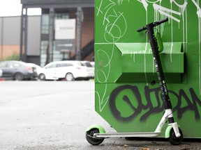 A Lime scooter is parked next to a Dumpster in Montreal on Aug. 21, 2019.