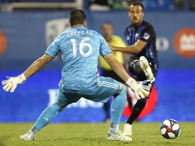 Maximiliano Urruti of the Montreal Impact crosses past Vancouver Whitecaps goalkeeper Maxime Crepeau. His pass set up an own-goal by Vancouver's Doneil Henry.