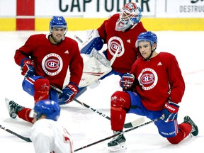 Ryan Poehling, left, goalie Cayden Primeau and Nick Suzuki follow Jake Evans's lead during stretching at Canadiens rookie camp workout at the Bell Sports Complex in Brossard.