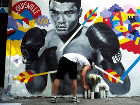 A man places a candle under a mural of the later boxer Muhammad Ali, who died in 2016 after a long battle with Parkinson's disease.