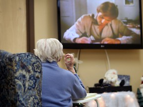 A elderly woman eats in front of a television at Wales Home on January 10, 2017.
