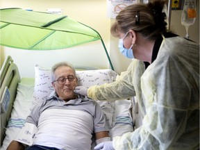 Christianne Robert gives some encouragement to her husband, Richard Vallières, moments before he is injected with his own genetically modified white blood cells that will attack his leukemia at Maisonnueve-Rosemont Hospital on Tuesday.