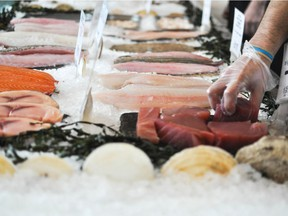 Fillets and whole fish for sale at a fish market.
