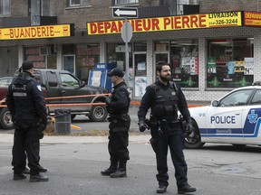 Montreal police stand outside one of the scenes of Thursday's shootings, at Matte Ave. and Pierre St. in Montreal North.
