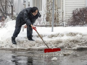 Zuan Zhu tries to clear water and ice from a drain in Lachine in January.