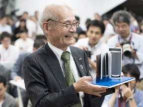 Akira Yoshino holds a model of a lithium-ion battery during a news conference in Tokyo. Yoshino won the 2019 Nobel Prize in chemistry with John B. Goodenough and M. Stanley Whittingham.