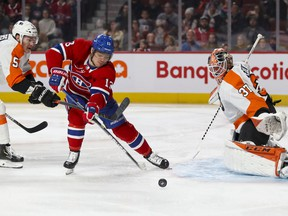 Canadiens' Max Domi has his stick lifted by Philadelphia Flyers Philippe Myers as he breaks in on goalie Brian Elliott in Montreal on Saturday, Nov. 30, 2019.