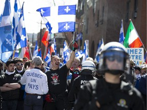 A group of Bill 21 protesters chant outside TVA with riot police watching in Montreal on May 4, 2019.