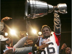 Alouettes' Ben Cahoon hoists the Grey Cup after parade down Ste-Catherine St. on Dec. 1, 2010.