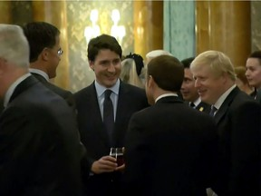 This grab made from a video shows Dutch Prime Minister Mark Rutte, left, French President Emmanuel Macron, front, British Prime Minister Boris Johnson, right, and Canada's Prime Minister Justin Trudeau, back-centre, as the leaders of Britain, Canada, France and the Netherlands were caught on camera at a Buckingham Palace reception mocking U.S. President Donald Trump's lengthy media appearances ahead of the NATO summit on Dec. 3, 2019, in London.