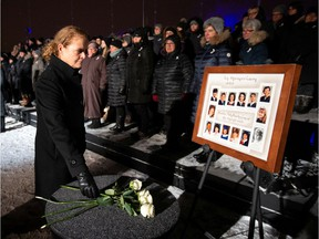 Canada's Governor General Julie Payette lays a white rose during a vigil on Friday, Dec. 6, 2019, on top of Mount Royal in front of a photo showing the 14 women who were killed in 1989. The ceremony marked the 30th anniversary of the mass shooting at École Polytechnique, in which 14 women who were killed and 14 were injured.