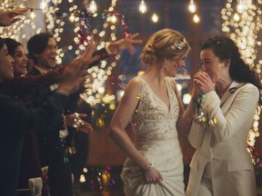 This image made from undated video provided by Zola shows a scene of its advertisement. Under pressure from a conservative advocacy group, The Hallmark Channel has pulled the ads for wedding-planning website Zola that featured same-sex couples, including two brides kissing. The family-friendly network, which is in the midst of its heavily watched holiday programming, removed the ads because the controversy was a distraction, a spokesperson said in an interview on Saturday, Dec. 14, 2019.