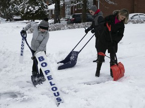 Elspeth Stilton and her children shovel a neighbour's driveway in Pointe-Claire on Jan. 1, 2020.