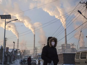 """Smoke billows from stacks as a woman walks in a neighbourhood next to a coal-fired power plant on November 26, 2015 in Shanxi, China. """"Make no mistake, when you buy something made in a country that relies heavily on electricity generated from coal, like China, you are contributing to carbonizing this planet,"""" Robert Fattal writes."""