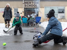 Five-year-olds Ethan Rosenshein, left, and goalie Ben Cytrynbaum pass the time Sunday in front of Merton School. Parents say the school should be included in a vaccination blitz being conducted by public health because the school is just a few blocks away from the designated zone.