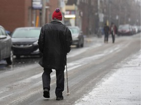 A visually impaired elderly man uses his white cane to follow the tire path on the street due to ice covered sidewalks in Montreal on Dec. 7, 2019.