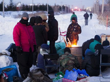 Protesters block the CN railway tracks near the St-Lambert train station south of Montreal early Friday, Feb. 21, 2020.