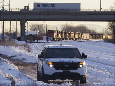 MONTREAL, QUE.: FEBRUARY 21, 2020 -- A CN police officer looks towards protesters blocking the CN railway tracks near the St-Lambert train station south of Montreal early Friday, Feb. 21, 2020. Behind is an idle freight train.