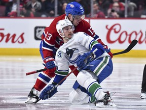 Canadiens's Max Domi takes down Canucks' Jay Beagle during second period Tuesday night at the Bell Centre.