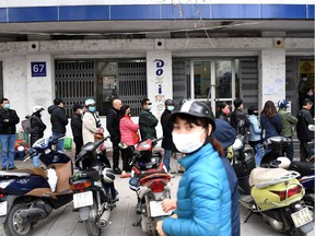 People line up to buy protective face masks amid concerns of the novel coronavirus outbreak that originated in central China, outside a shop in Hanoi on February 10, 2020.