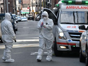 South Korean medical workers wearing protective gear carry samples as they visit a residence of people with suspected symptoms of the COVID-19 coronavirus, near the Daegu branch of the Shincheonji Church of Jesus in Daegu on February 27, 2020. -