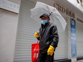 A man wears a face mask in a deserted shopping street in Jiujiang, Jiangxi province, China, as the country is hit by an outbreak of the novel coronavirus, on Sunday, Feb. 2, 2020.