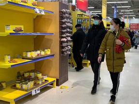Shoppers wearing masks walk by depleted shelves at the Maxi store in Pointe-Claire on March 13, 2020.