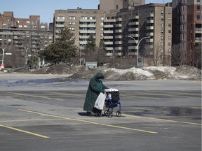 Carmen Larivière, 95, crosses a nearly empty parking lot at the Cavendish Mall in Côte-St-Luc on Saturday, March 21, 2020 after buying some supplies. She lives alone in Côte-St-Luc.