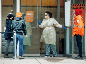 A nurse speaks to people asking for a COVID-19 test at St. Michael's Hospital in Toronto, March 30, 2020.