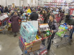 Customers lineup at the checkout area at a Costco store on March 13, 2020, in Montreal.