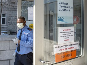 A security guard wears a protective mask in front of the new COVID-19 clinic at the site of the former Hotel Dieu hospital on March 9, 2020 in Montreal.